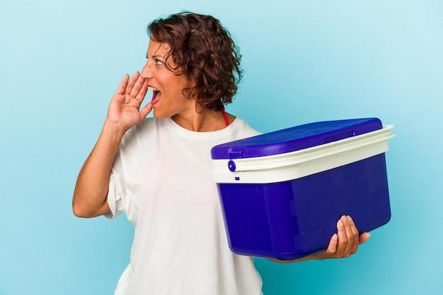 Femme latine d'âge moyen isolée sur fond bleu criant et tenant la paume près de la bouche ouverte.