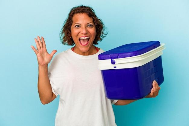 Femme latine d'âge moyen isolée sur fond bleu recevant une agréable surprise, excitée et levant les mains.