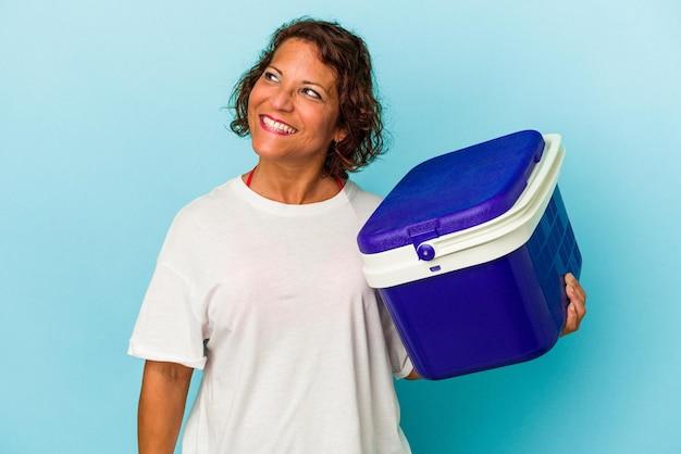 Femme latine d'âge moyen isolée sur fond bleu rêvant d'atteindre des objectifs et des buts
