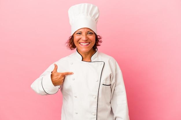 Femme latine d'âge moyen isolée sur fond rose personne pointant à la main vers un espace de copie de chemise, fière et confiante