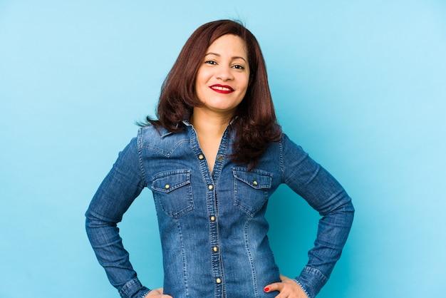 Femme latine d'âge moyen isolée sur un mur bleu confiant en gardant les mains sur les hanches.