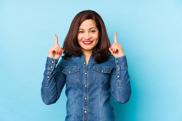 Femme latine d'âge moyen isolée sur un mur bleu indique avec les deux doigts avant montrant un espace vide