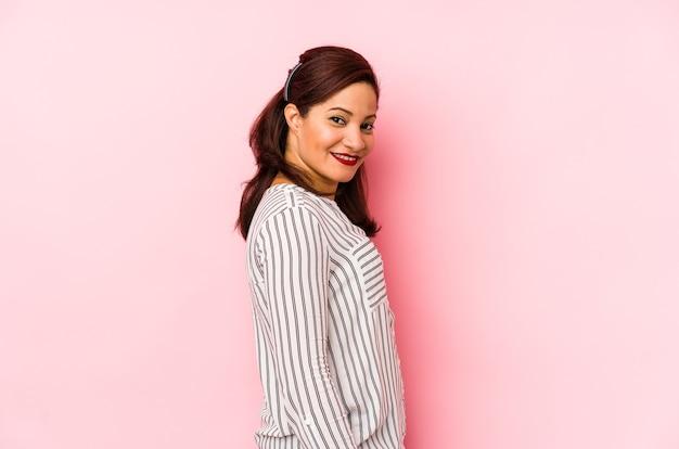Femme latine d'âge moyen isolée sur un mur rose regarde de côté souriant, joyeux et agréable