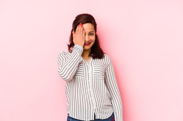 Femme latine d'âge moyen isolée sur un mur rose s'amusant couvrant la moitié du visage avec palm