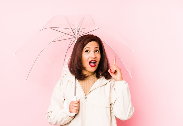 Femme latine d'âge moyen portant un parapluie isolé pointant à l'envers avec la bouche ouverte.