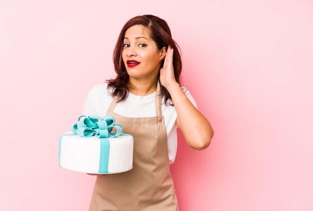 Femme latine d'âge moyen tenant un gâteau isolé sur fond rose essayant d'écouter les potins.