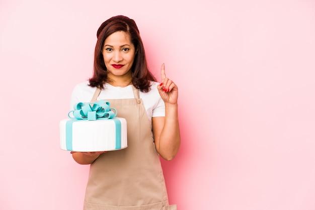 Femme latine d'âge moyen tenant un gâteau isolé sur un mur rose montrant le numéro un avec le doigt.