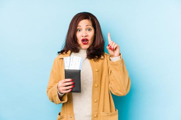 Femme latine d'âge moyen tenant un passeport isolé ayant une bonne idée, concept de créativité