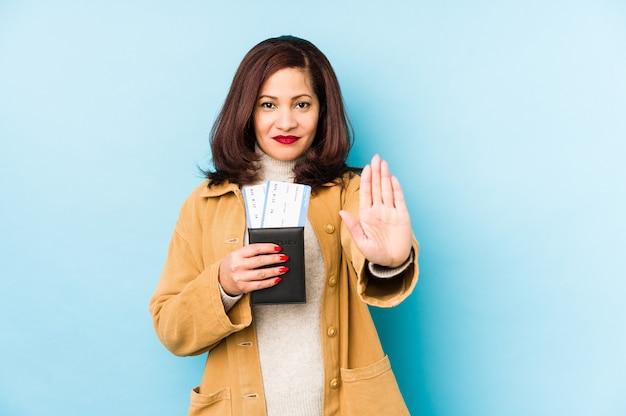Femme latine d'âge moyen tenant un passeport isolé debout avec la main tendue montrant le panneau d'arrêt, vous empêchant.
