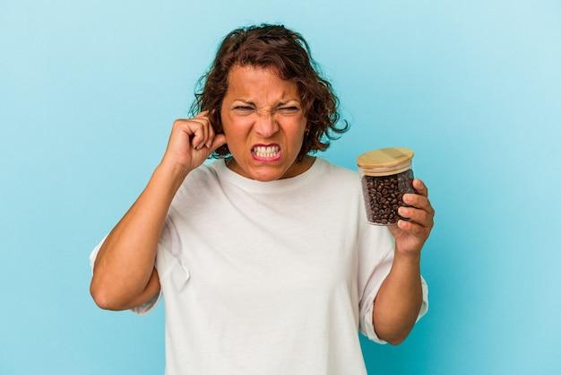 Femme latine d'âge moyen tenant un pot de café isolé sur fond bleu couvrant les oreilles avec les mains.