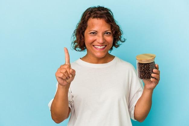 Femme latine d'âge moyen tenant un pot de café isolé sur fond bleu montrant le numéro un avec le doigt.