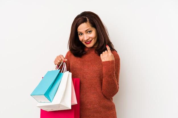 Femme latine d'âge moyen tenant un sacs à provisions isolés pointant avec le doigt sur vous comme si vous invitiez à vous rapprocher