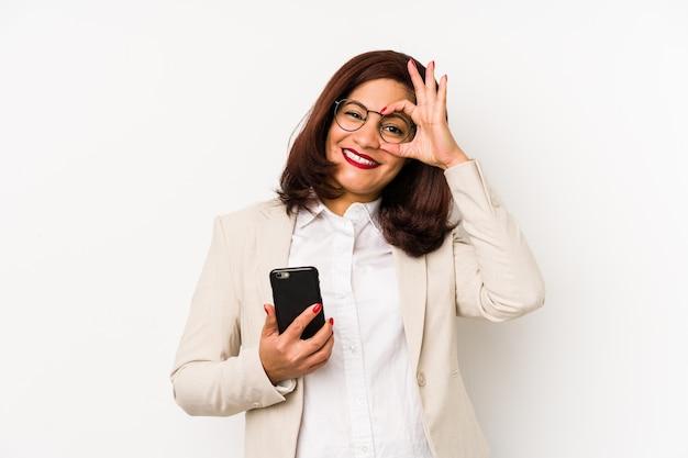 Femme latine d'âge moyen tenant un téléphone mobile isolé excité en gardant le geste ok sur les yeux