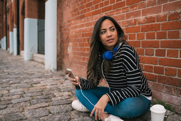 Femme latine à l'aide de téléphone portable.