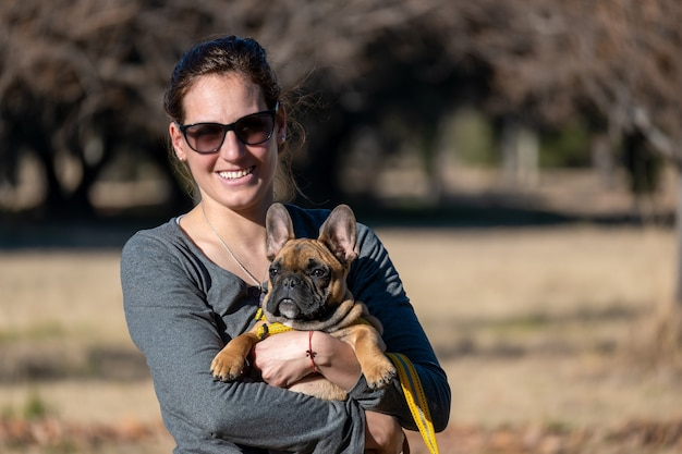 Femme latine, avec chien bouledogue français dans le parc.