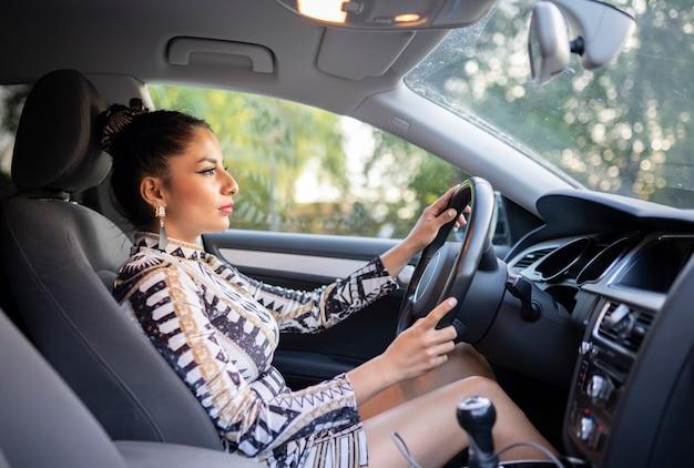 Femme latine conduisant une voiture à l'intérieur