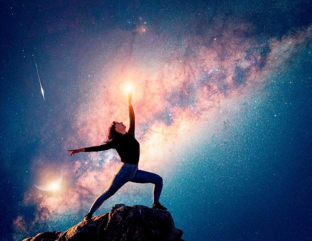 Femme latine danse ou pose au sommet de la montagne pointant vers le ciel et la voie lactée