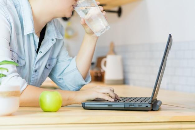 Femme latine de l'eau potable tout en utilisant son ordinateur portable