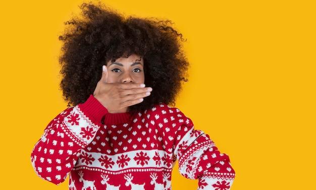 Femme latine hispanique aux cheveux bouclés à noël couvrant sa bouche surprise, fond jaune