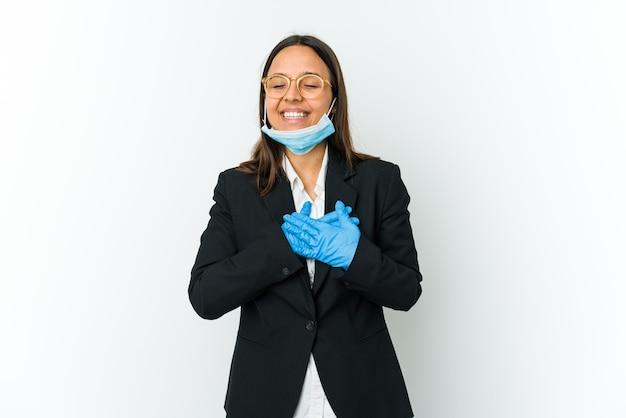 Femme latine jeune entreprise portant un masque pour se protéger de covid isolé sur fond blanc en riant en gardant les mains sur le cœur, concept de bonheur.