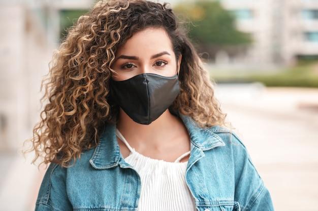 Femme latine portant un masque facial tout en se tenant à l'extérieur dans la rue concept urbain