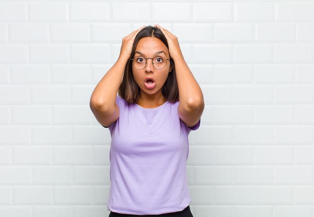 Femme latine à la recherche excitée et surprise, bouche bée avec les deux mains sur la tête, se sentant comme un heureux gagnant