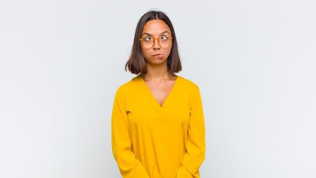 Femme latine à la recherche maladroite et drôle avec une expression idiote aux yeux croisés, plaisantant et s'amusant