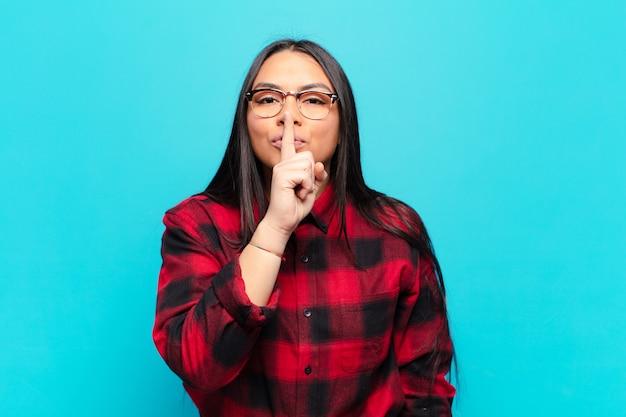 Femme latine à la recherche sérieuse et croisée avec le doigt pressé sur les lèvres exigeant le silence ou le calme, gardant un secret
