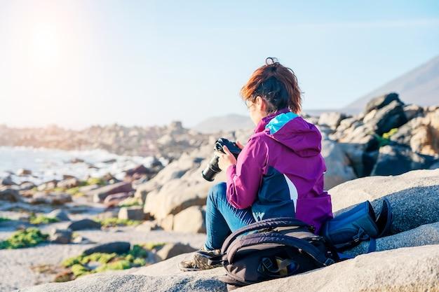 Femme latine avec sac à dos prenant des photos sur la plage rocheuse
