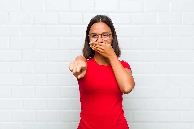 Femme latine se moquant de vous, pointant vers la caméra et se moquant ou se moquant de vous