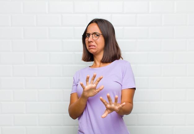 Femme latine se sentant dégoûtée et nauséeuse, s'éloignant de quelque chose de méchant, malodorant ou puant, disant beurk