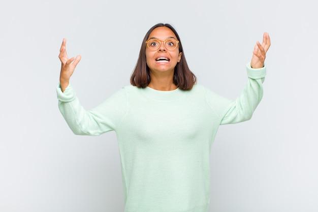 Femme latine se sentant heureuse, étonnée, chanceuse et surprise, célébrant la victoire avec les deux mains en l'air
