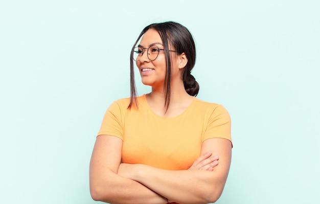 Femme latine se sentant heureuse, fière et pleine d'espoir, se demandant ou pensant, levant les yeux pour copier l'espace avec les bras croisés