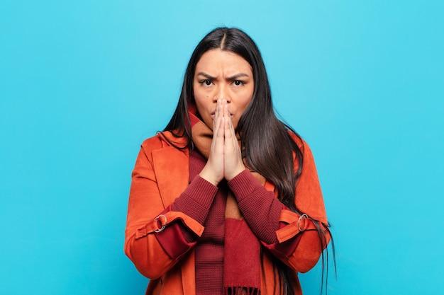 Femme latine se sentant inquiète, bouleversée et effrayée, couvrant la bouche avec les mains, regardant anxieuse et ayant foiré