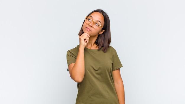 Femme latine se sentant réfléchie, se demandant ou imaginant des idées, rêvassant et levant les yeux pour copier l'espace