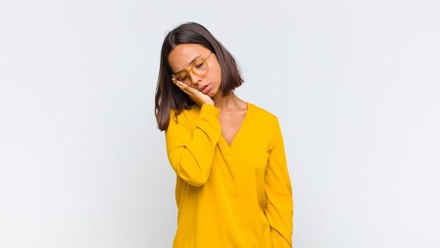 Femme latine se sentir ennuyé, frustré et somnolent après une tâche fastidieuse, ennuyeuse et ennuyeuse, tenant le visage avec la main