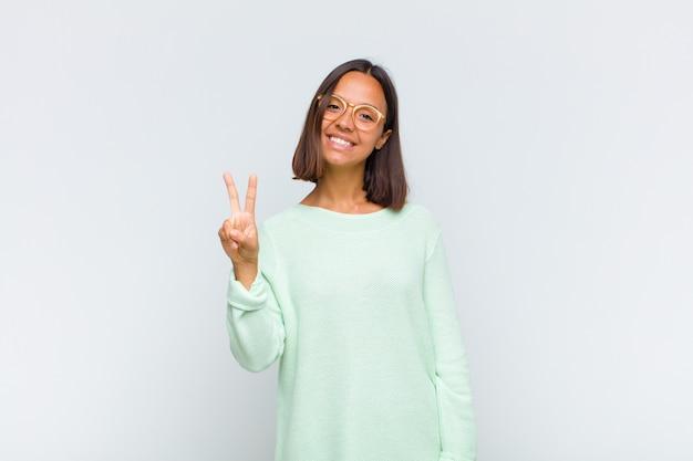 Femme latine souriante et à la recherche heureuse, insouciante et positive, gesticulant la victoire ou la paix d'une seule main