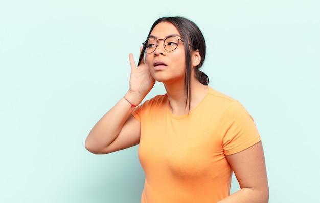 Femme latine souriante, regardant curieusement sur le côté, essayant d'écouter des ragots ou d'entendre un secret