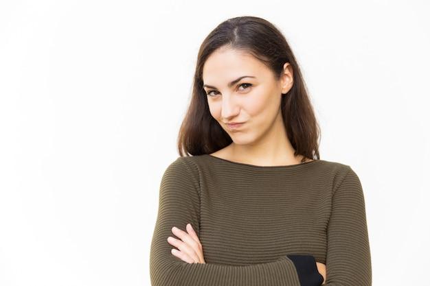 Femme latine souriante sournoise avec les bras croisés