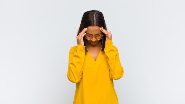 Femme latine à la stress et frustré, travaillant sous pression avec un mal de tête et troublé par des problèmes