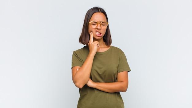 Femme latine tenant la joue et souffrant de maux de dents douloureux, se sentir malade, misérable et malheureux, à la recherche d'un dentiste