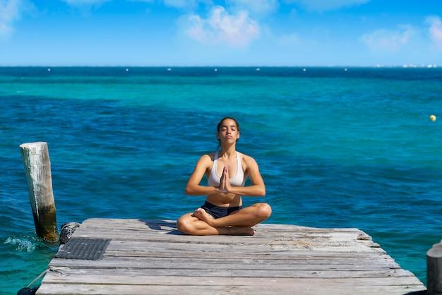 Femme latine yoga relaxant dans les caraïbes