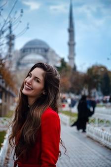 Femme latino-américaine ou femme turque dans un manteau élégant rouge en face de la célèbre mosquée bleue à istanbul