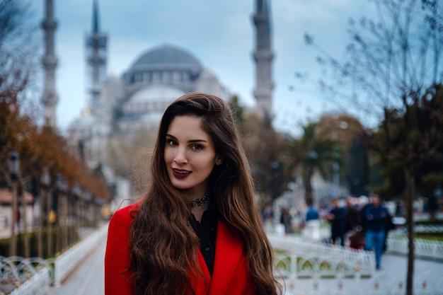 Femme latino-américaine ou femme turque dans un manteau rouge élégant devant la célèbre mosquée bleue d'istanbul, photo d'un voyageur sur le fond d'une mosquée le jour de l'automne.