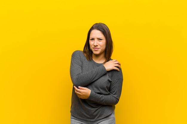 Femme latino-américaine se sentant anxieuse, malade, malade et malheureuse, souffrant de maux d'estomac douloureux ou grippe isolée contre le mur jaune
