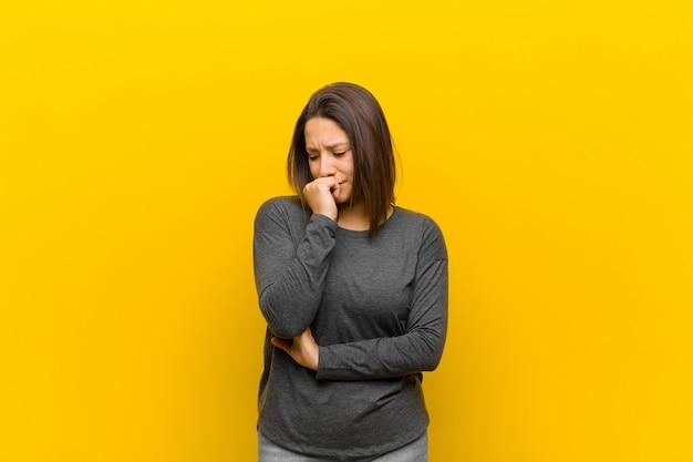 Femme latino-américaine se sentant sérieuse, réfléchie et inquiète, regardant de côté avec la main pressée contre le menton contre le mur jaune