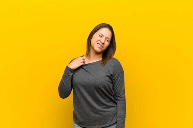 Femme latino-américaine se sentant stressée, anxieuse, fatiguée et frustrée, tirant sur le cou de la chemise, frustrée par le problème isolé contre le mur jaune
