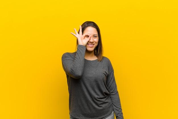 Femme latino-américaine souriant joyeusement avec grimace, plaisantant et regardant à travers un judas, espionnant des secrets isolés contre le mur jaune