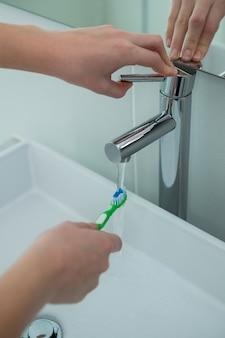 Femme, lavage, brosse dents, sous, évier, salle bains