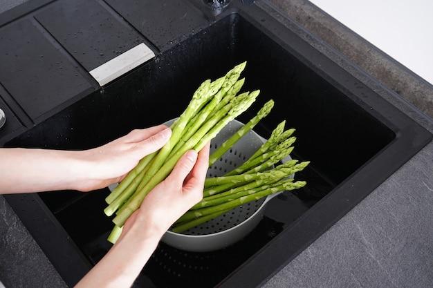 Femme lavant les asperges crues fraîches sur l'évier, vue de dessus. surface pour la gastronomie et l'art de vivre.